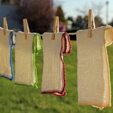 4 dura fresh cloths hanging on clothesline outdoors. threading includes blue, green, red and yellow