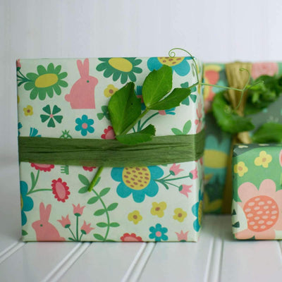 gifts with wrappily wrapping paper, enchanted garden design, tied with green ribbon and plant leaves