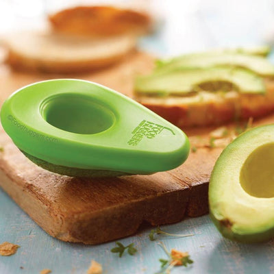 avocado hugger on ripe avocado, next to sandwich being make on wooden cutting board