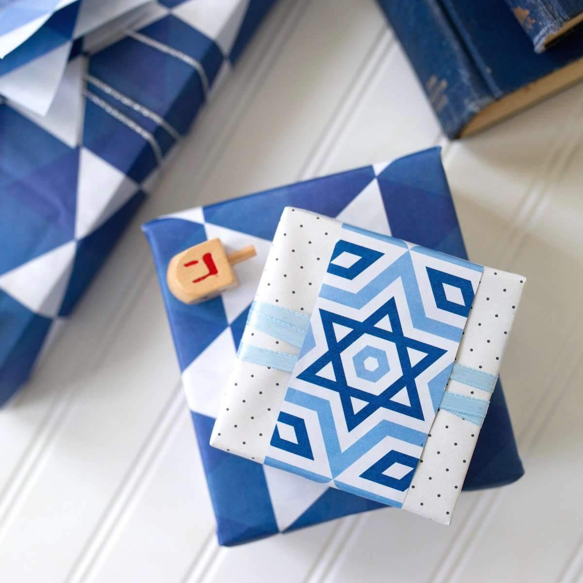 two packages wrapped in Hannukah paper with a dradle on top
