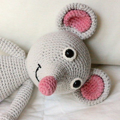 close up of knitted smiling mouse toy with pink nose and pink ears. displayed on bed with white sheets
