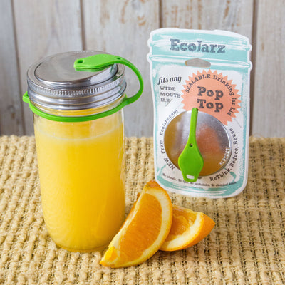 orange juice in mason jar with eco jarz lid and green pop top, orange slices and eco jarz packaging