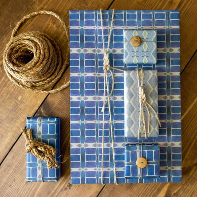 stacked gifts with wrappily wrapping paper, riptide design, tied with twine in sailor knots on wooden table next to spool of heavy twine