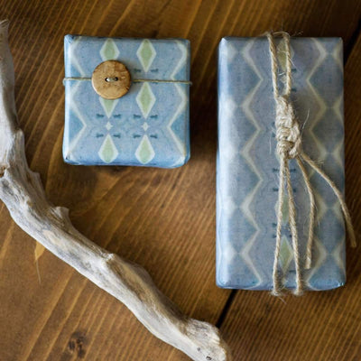two gifts wrapped with wrappily paper riptide design. twine, wood button, drift wood and wooden table