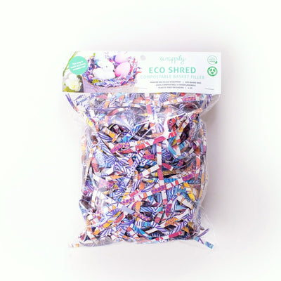 plastic bag filled with compostable basket filler. multicolored/patterned shredded paper.