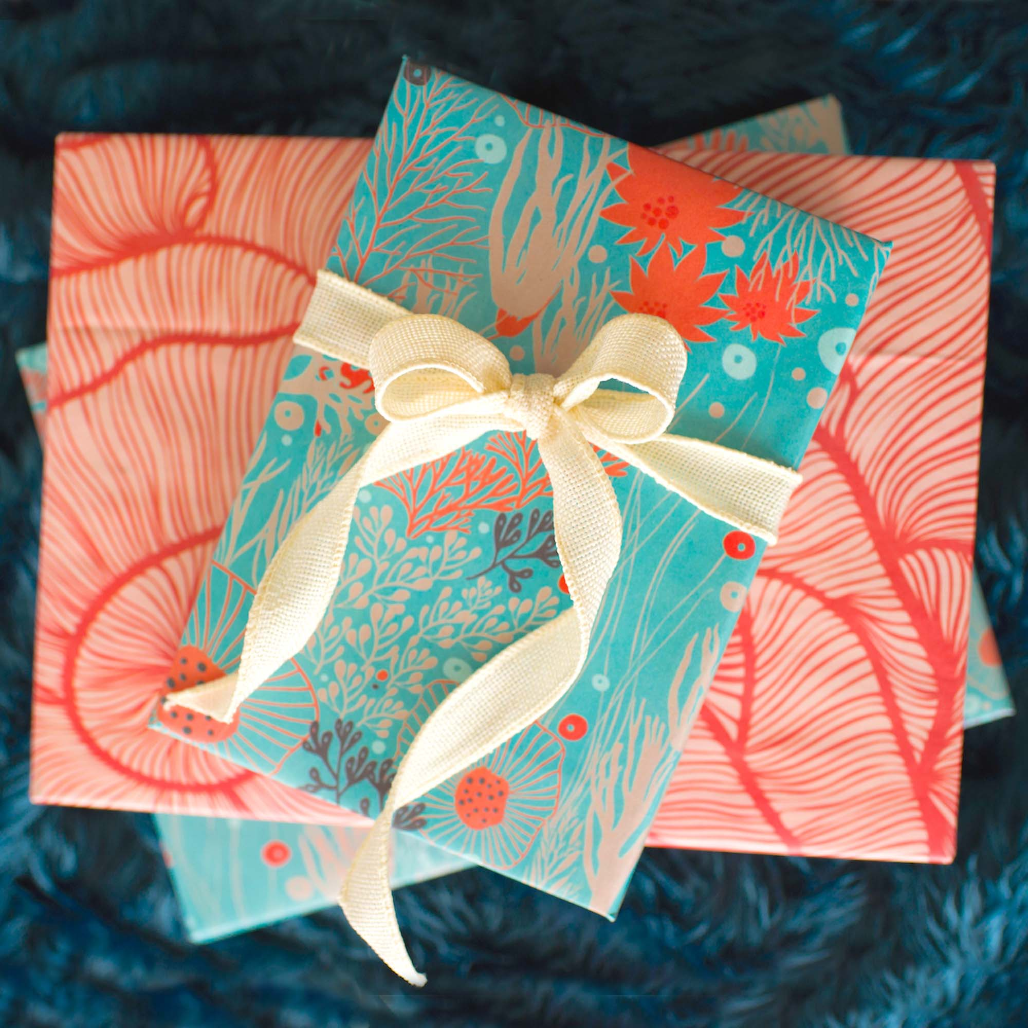 gifts stacked with wrappily wrapping paper, underwater flora design, reversible blue and red, white think ribbon tied into bow
