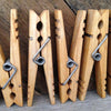 close up of 5 clothespins displayed vertically in front of rustic reclaimed wood