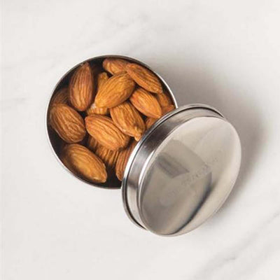 round stainless steel container with metal lid ajar, contains almonds