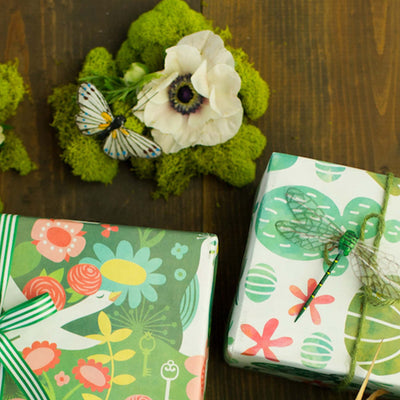 two gifts, wrapped with wrappily enchanted garden paper on dark wooden tabletop