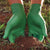 Pair of hands wearing green nitrile gloves, digging in the dirt
