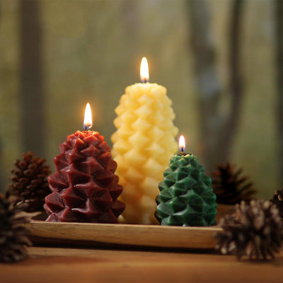 three lit pine cone candles (red, natural, green) on a table with real pinecones