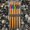 5 pairs of bamboo chopsticks with a colorful square pattern on the top third of each chopstick.