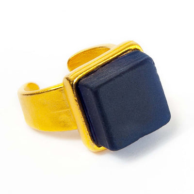 Close up of a dark blue recycled glass cocktail ring with a gold band and a square stone