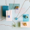 Square recycled glass pendant necklaces and three gold band recycled glass rings (shades of blue)