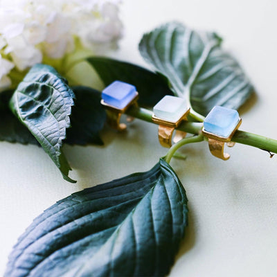 Three gold band rings with square blue stones sitting on the stem of a cut hydrangea