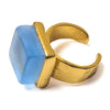 Close up of a blue recycled glass cocktail ring with a gold band and a square stone