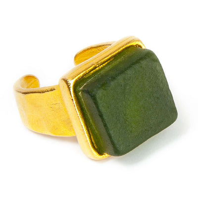 Close up of a dark green recycled glass cocktail ring with a square stone and agold band