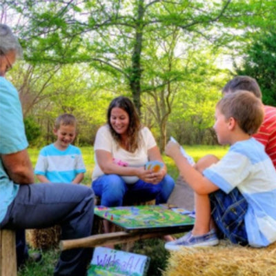 two adults and three children sit outdoors on hay bails, playing wildcraft game, happy