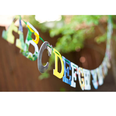 Alphabet displayed hanging outside in sunny backyard party