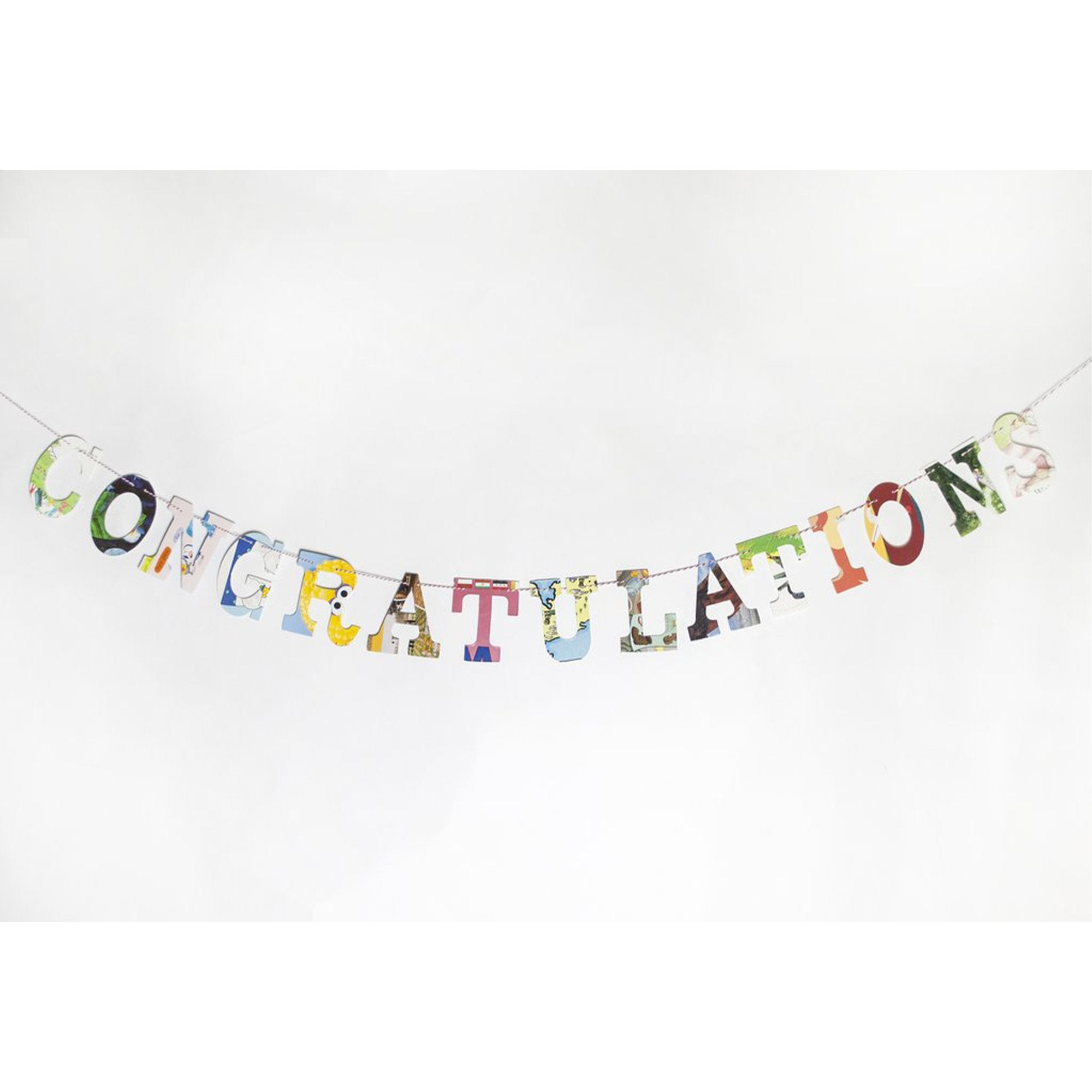 """Congratulations"" garland, multi colored collage style, hanging on white wall"