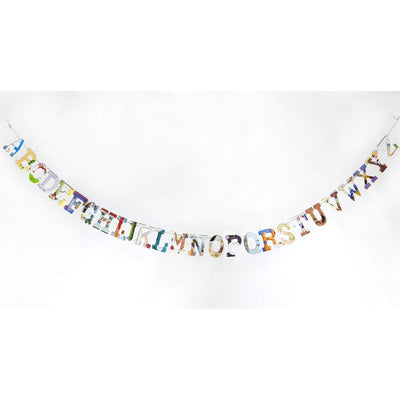 multi-colored, collage style alphabet garland displayed  hanging on white wall