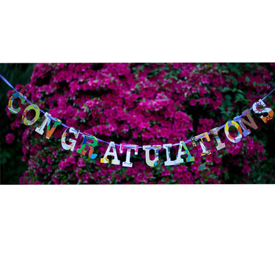 "Multicolored, collage style ""congratulations"" hanging outdoors in front of flowery pink shrub in full bloom"