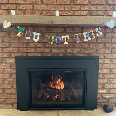 "multicolored ""you got this"" with hearts garland, hanging over brick fireplace indoors"