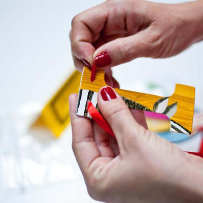 "womens hands with red nail polish, threading red ribbon through the letter ""I"", constructing a custom garland"