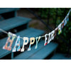 "multicolored collage style ""Happy Birthday"" garland, hanging over outdoor back porch green wooden stairs with black metal railing"