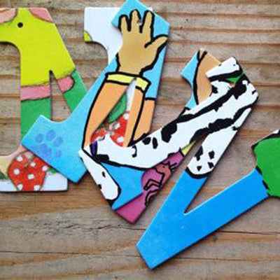 "Three different designs of the letter ""N"" placed on unfinished wood. Designs feature pages of children's picture books"