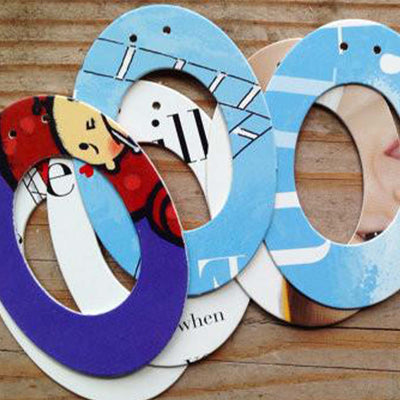 "six designs of the letter ""O"", placed on exposed wood. Each design uses pages from children's picture books"