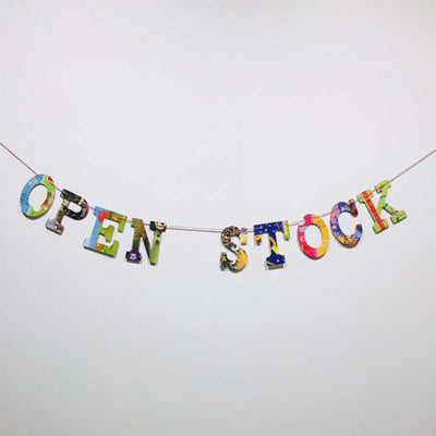 "multi-colored, collage style ""open stock"" garland displayed  hanging on white wall"