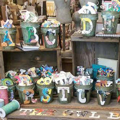 metal buckets placed on wooden crates  containing letters A-D and R-V, alongside spools of multicolored ribbon,  Each bucket is overflowing with a variety of designs of each letter.