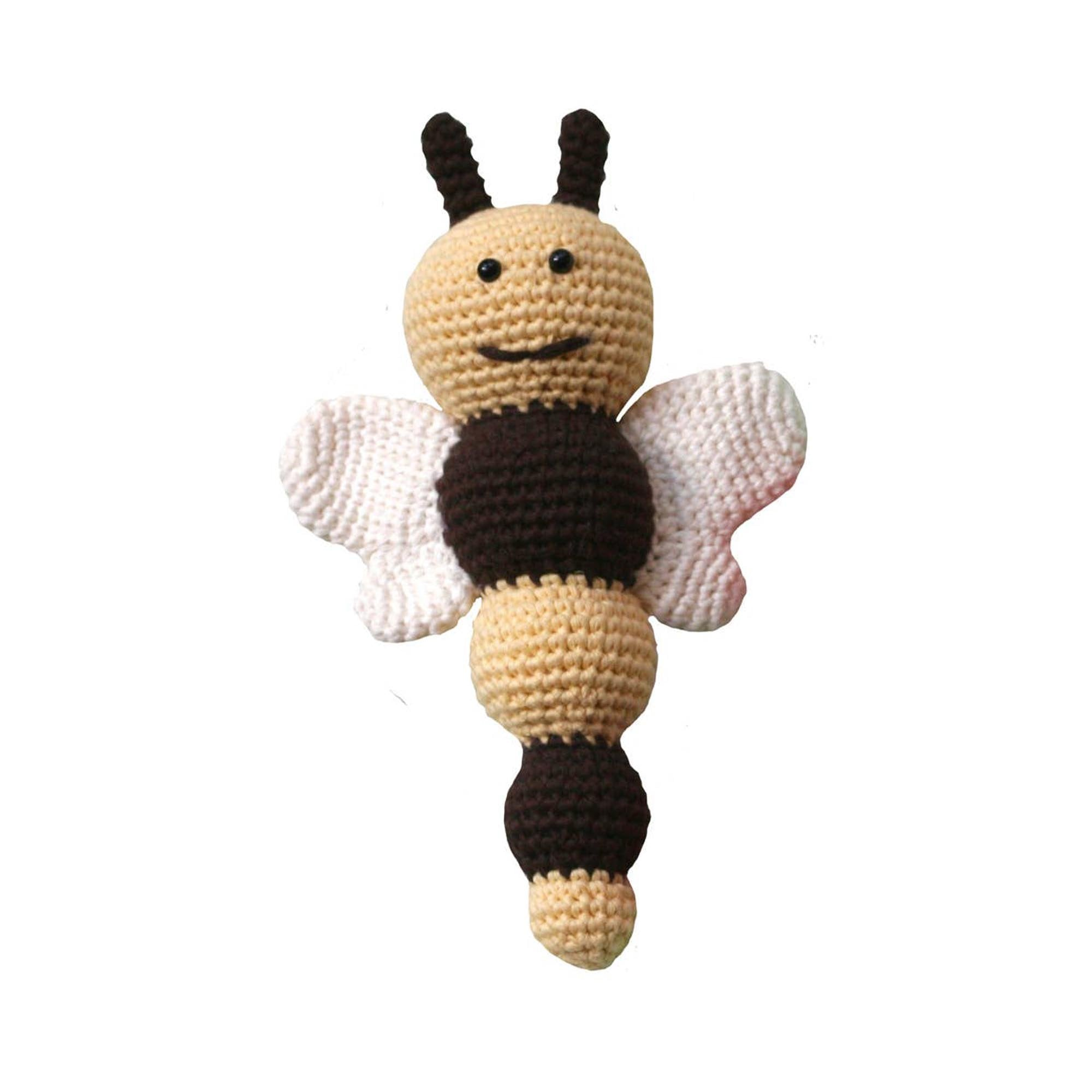 handmade, knitted baby rattle, shaped like a smiling bumble bee, soft earth tone colors displayed on white backdrop