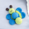 knitted blue and green baby rattle shaped like a smiling butterfly