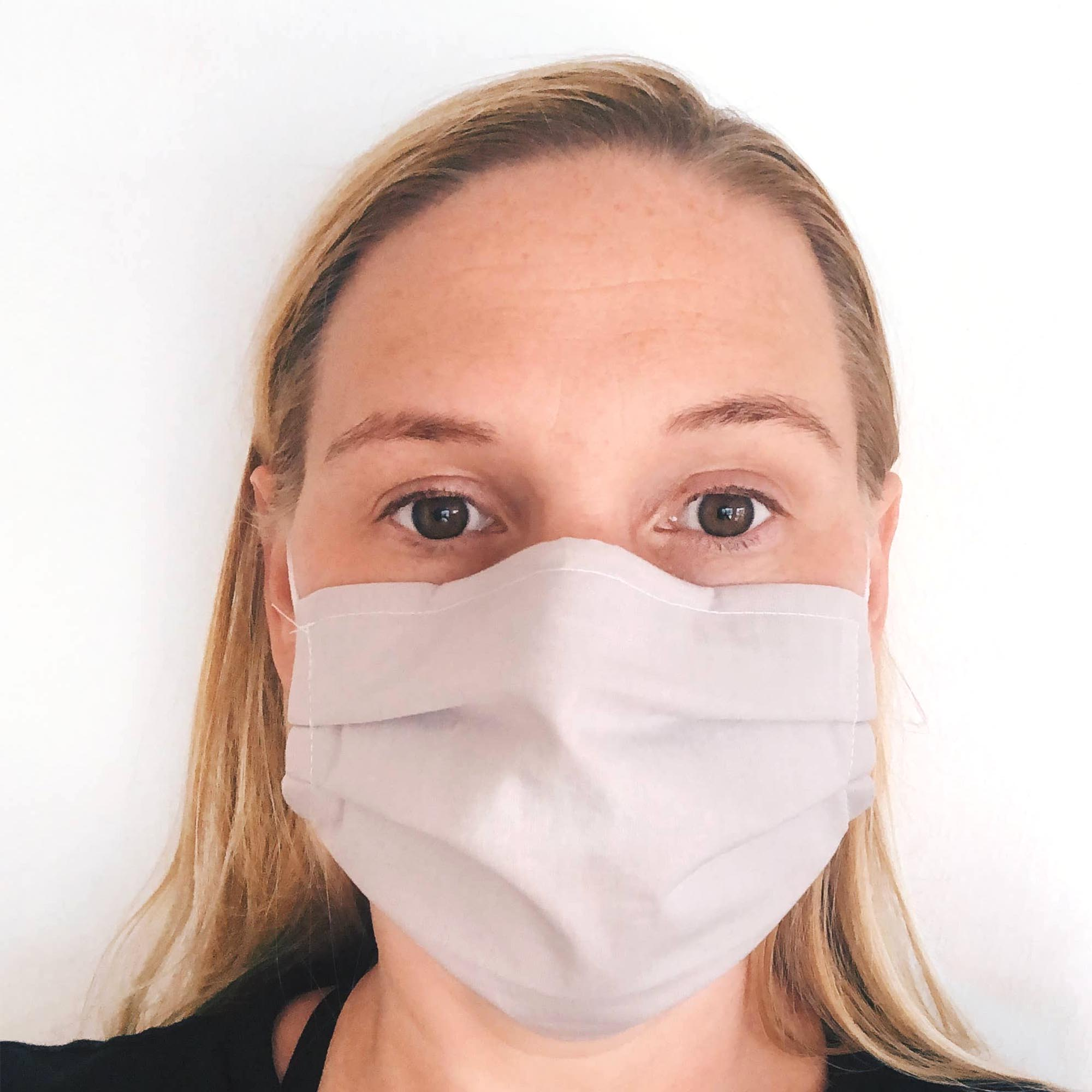 blonde women with brown eyes, wearing grey face mask in front of white backdrop