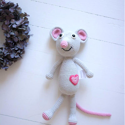 knitted grey mouse toy with heart symbol on white painted wooden table top, alongside violet wreath