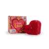 Ruby red heart pillar candle with floral relief, leaning on cardboard packaging with words Pure Love on front
