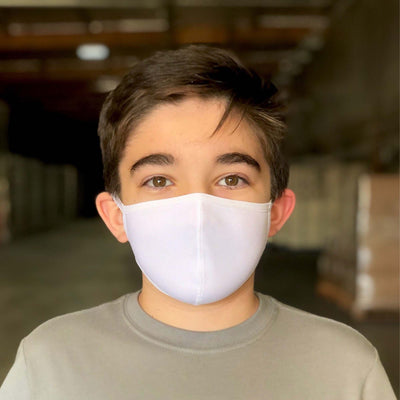 Young brown haired boy wearing grey shirt and white reusable organic face mask, standing in warehouse