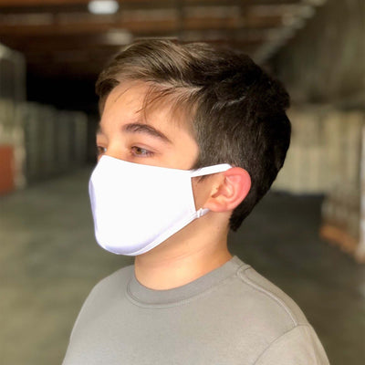 Young brown haired boy wearing grey shirt and white reusable organic face mask, standing in warehouse, facing sideways showing straps of mask around his ear