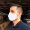 young man with short hair and dark blue collared shirt, wearing white reusable organic face mask, standing in warehouse facing sideways showing straps around ear