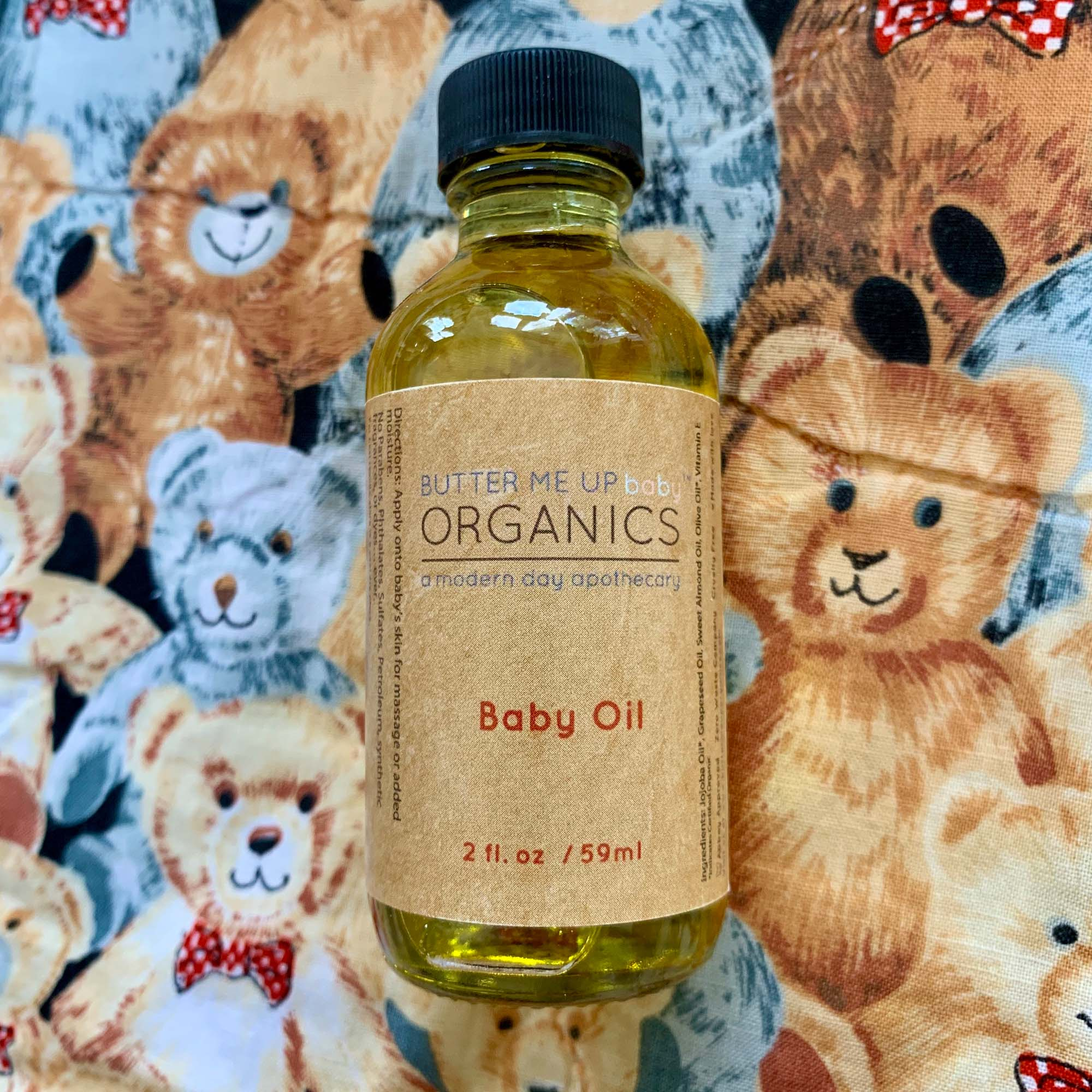 2 fl oz baby oil in clear container displayed in front of illustration of teddy bears