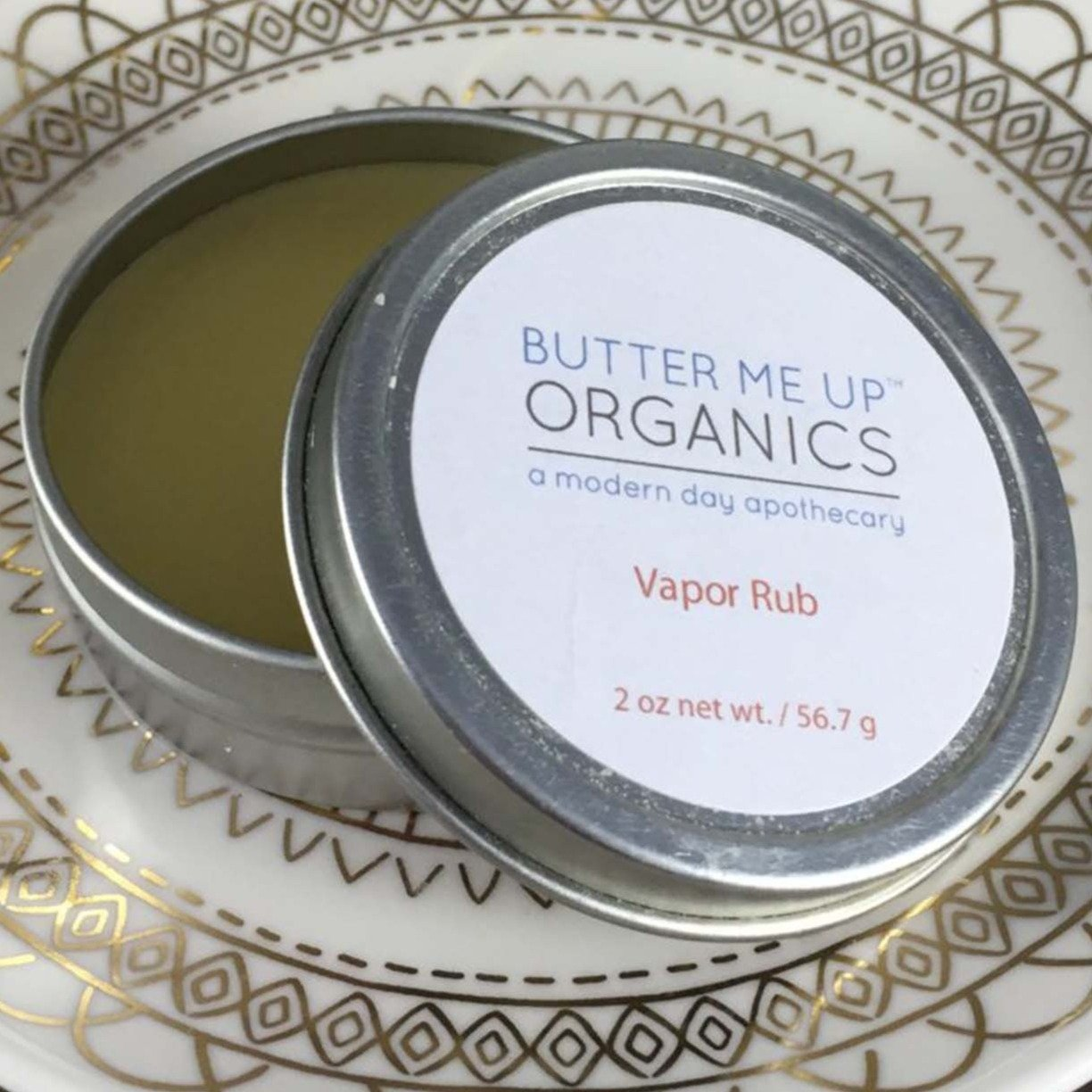 2 oz vapor rub in circular tin with lid ajar.
