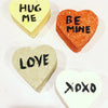 "4 heart shaped bath bombs, black handwritten words, ""hug me"" on yellow heart, ""be mine"" on red heart, ""love"" on brown heart, ""xoxo"" on white heart"