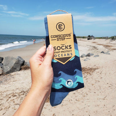 hand holding blue ocean themed socks on beach with sand and waves in background