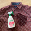 pink floral design spray bottle, 16.9 fl oz, laundry pre spray, with red and white polka dot shirt with stain on front pocket.