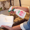 womans hands with pink nails spraying laundry pre spray onto white towel with dirt stain over sink