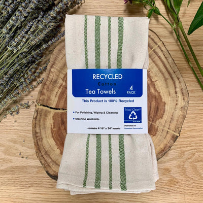 4 pack of creme and green striped cotton tea towels, displayed with calming herbs and exposed wood
