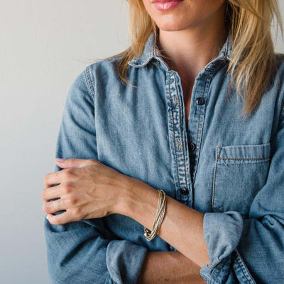blonde woman in denim shirt, sleeves rolled up, wearing bullets to beads bracelet on left wrist