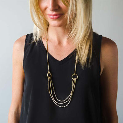 blonde women in black tank top wearing low hanging ombre layer necklace
